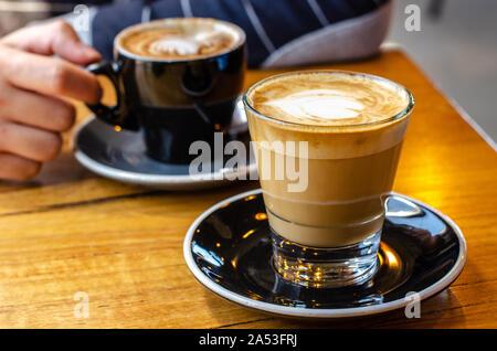 Gros plan sur une tasse de café latte avec un fond flou de la main d'un homme tenant son café sur le côté opposé de la table.