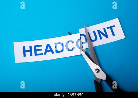 L'effectif à l'aide de ciseaux de coupe personne sur fond bleu Banque D'Images