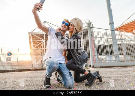 Couple de jeunes amateurs de beaux selfies prendre sur la grande place d'un stade