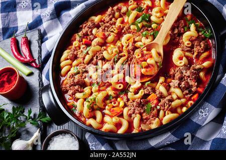 Close-up of american italian goulash de elbow macaroni, le boeuf, le céleri et les tomates dans un plat de céramique noire sur une table en bois avec des essuie-tout, voir f Banque D'Images