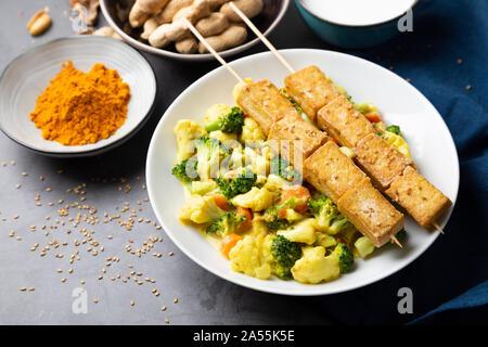 Satay Tofu sauté de légumes, épices et de graines dans un plat sur un fond de pierre Banque D'Images
