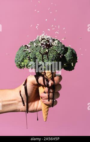 Studio shot of man's hand holding ice cream cone avec brocoli sur le dessus, des gouttes de sauce au chocolat et sprinkles, contre fond rose
