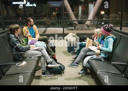 Homme mature avec fils et fille en attente dans la salle d'embarquement de l'aéroport de manger des collations