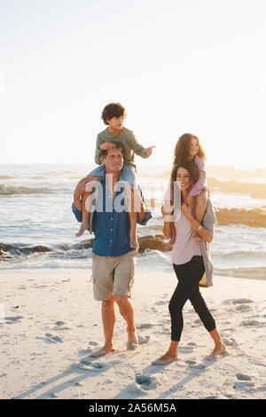 Couple giving children piggyback ride on beach Banque D'Images