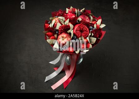Composition unique sous la forme d'un bouquet de grenades, pommes, fraises, groseilles rouges et roses sur fond noir Banque D'Images