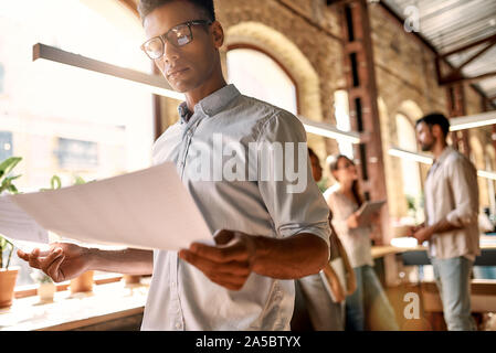 Travailler sur de nouveaux projets. Homme jeune dans les tenues de l'analyse des documents tout en se tenant dans le bureau moderne