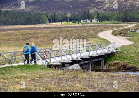 Deux femmes marchant sur la passerelle en bois sur la rivière à la montagne écossaise Muick Corbett Conachcraig de Spittal de Glenmuick, Glen Muick, Banque D'Images