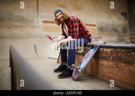 Portrait d'homme barbu contemporain looking at camera et souriant tout en utilisant l'emplacement du smartphone sur la rampe en skating park, copy space Banque D'Images