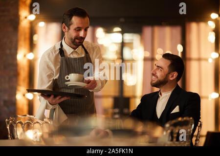 Side view portrait of handsome businessman talking to barbu portant restauration café et restaurant de luxe souriant joyeusement dans Banque D'Images