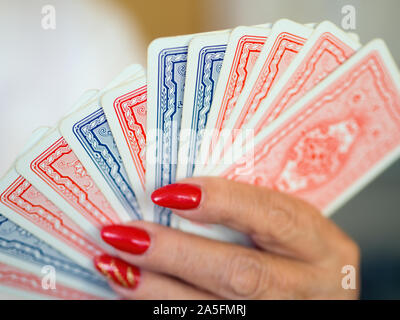 Cartes à jouer en bleu et rouge avec design l'arrière alignés dans une main féminine avec des clous laqué rouge. Se concentrer sur le reste, Point light Bookeh. Close-up Banque D'Images