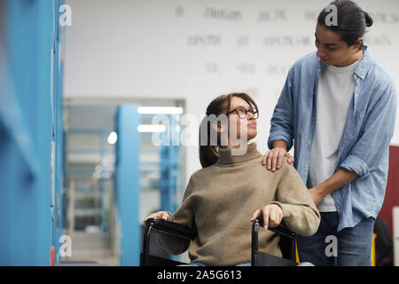 Portrait of young couple, femme en fauteuil roulant, à l'un l'autre et souriant tout en se tenant par les étagères de bibliothèque Banque D'Images