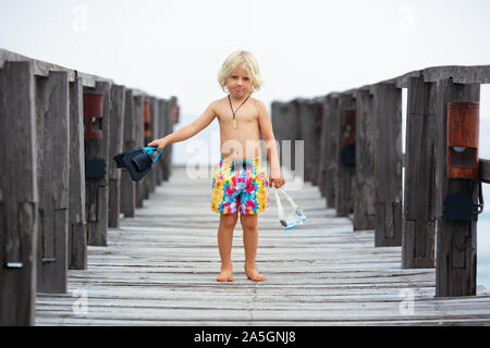 Heureux petit enfant avec masque, palmes et tuba pour aller plonger en mer tropicale à l'exploration de la nature sous-marine. Style de voyage, sports aquatiques, natation. Banque D'Images