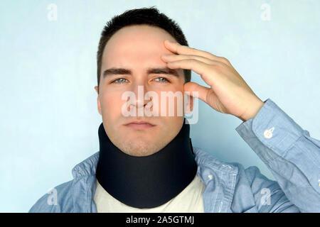 Un type avec un mauvais cou dans un cou noir collier pour stabiliser les vertèbres cervicales. Un homme avec une blessure au cou sur un fond bleu. fracture vertébrale de la tête. Banque D'Images