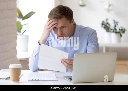 Souligné middle aged businessman reading paper document avec de mauvais résultats. Banque D'Images
