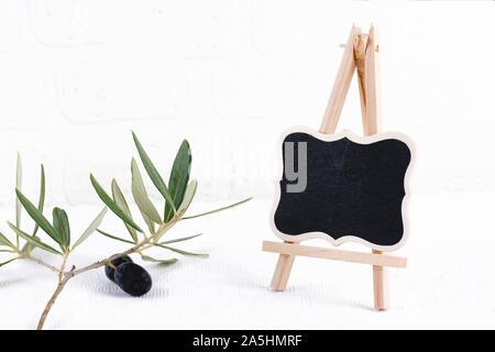 Chalk board stand extérieur vierge immersive avec branche d'olivier sur fond blanc mur de brique. La signalisation de la rue vide ou tableau noir modèle avec cadre en bois