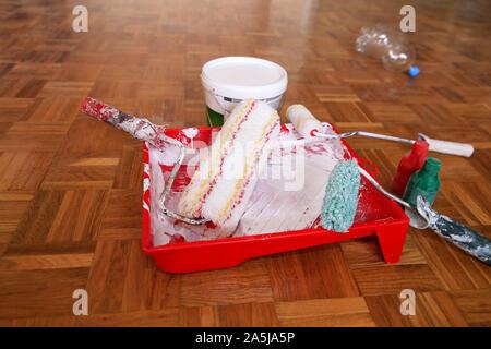 La peinture murale de l'équipement et des outils. Seau avec de la peinture blanche, couleur de peinture rouge et vert bouteille, bol mélangeur de peinture rouge pour rouleau à peinture et le rétrécissement de la paroi Banque D'Images