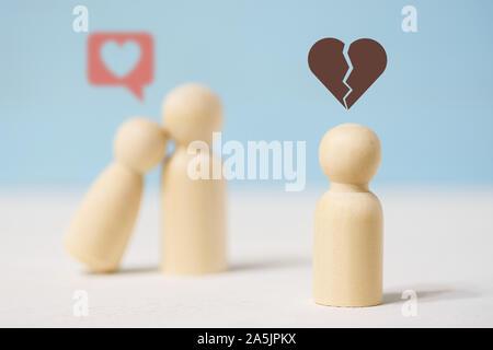 Close up of sad seul figure en bois est à la recherche sur le couple amoureux sur fond bleu. Banque D'Images