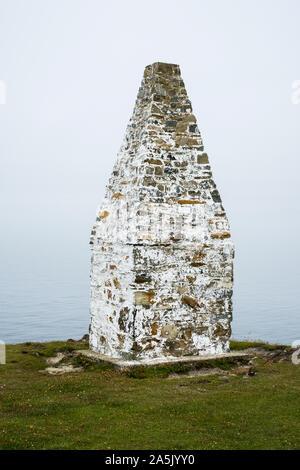 La baie de Cardigan et cairn de pierre marquant à l'entrée du port de Porthgain Sentier de Pembrokeshire Coast National Park, Pembrokeshire, Pays de Galles, Royaume-Uni. Banque D'Images