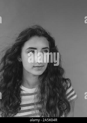 Portrait noir et blanc de la jolie fille de seize ans, le vent souffle à la longue chevelure ondulée Banque D'Images