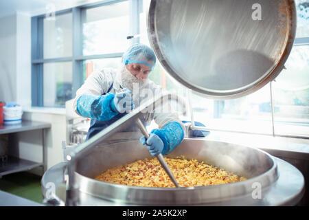 En remuant travailleur lot de nourriture en usine alimentaire Banque D'Images