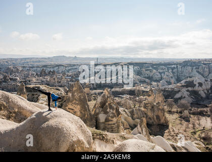 Woman practicing yoga on top of rock, Göreme, Cappadoce, Nevsehir, Turquie Banque D'Images