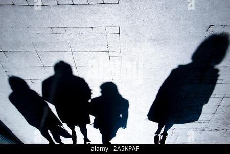 Silhouette ombre floue de gens qui marchent dans la nuit, et d'une femme seule, le trottoir de la rue de la ville en noir et blanc à contraste élevé Banque D'Images