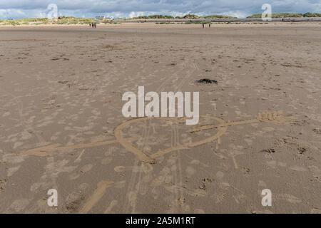 Coeur avec une flèche tracée dans le sable à Crosby Beach, près de Liverpool, Merseyside, Royaume-Uni Banque D'Images