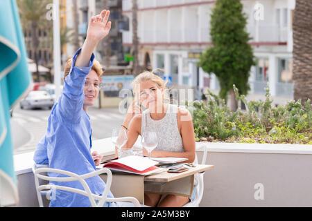 Jolies jeunes cheveux blonds levant la main tout en restant assis table partage avec son petit ami. Banque D'Images