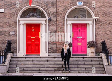 Jeune femme sur l'escalier en face de bâtiment résidentiel, Dublin, Irlande Banque D'Images