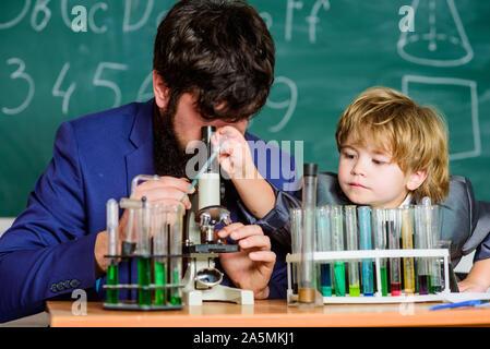 L'activité d'enseignement de l'étude par l'expérience. J'aime étudier dans l'école. Enseignant et garçon en laboratoire de chimie. Étudier la chimie et la biologie. L'étude est intéressante. L'exemple personnel et d'inspiration. Banque D'Images