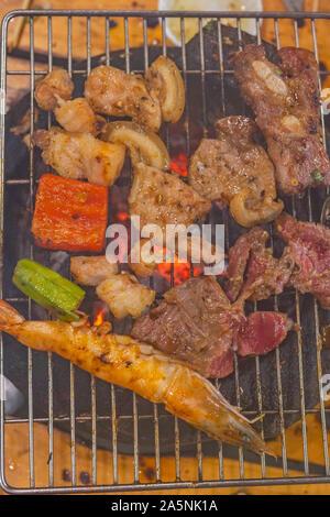 Photo verticale de viandes et les crevettes sur le gril de charbon cuisinière Banque D'Images