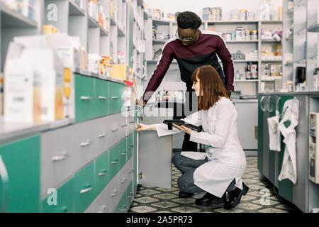 Jeune homme africain demande client jolie jeune femme pharmacien sur les médicaments en apothicaire. Femme docteur est à la drogue sur des étagères Banque D'Images