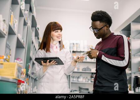 Jeune homme africain demande client Pretty woman à votre pharmacien au sujet des médicaments en apothicairerie Banque D'Images