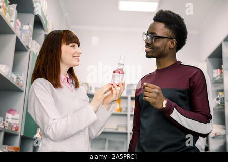 Femme médecine pharmacien recommande pour les jeunes homme africain client en pharmacie. Banque D'Images