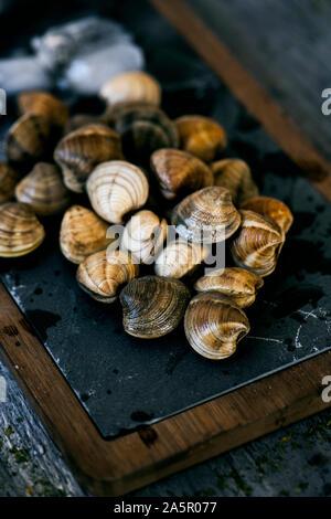 Libre de certaines matières les palourdes, entouré de glace pilée, sur un plateau en bois et ardoise noire, placé sur une table en bois rustique gris Banque D'Images