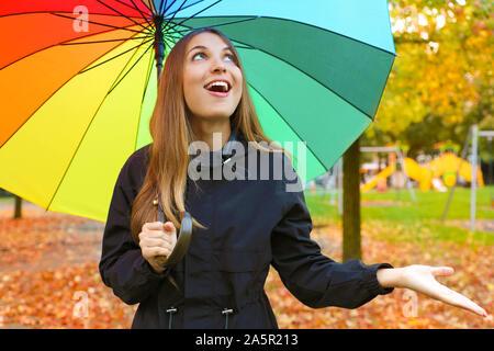 Rire jeune femme avec parapluie colorés pour contrôler la pluie. Banque D'Images