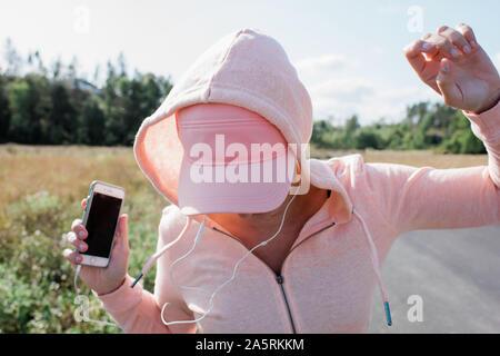 Femme tenant son téléphone et écouteurs dancing à l'extérieur du pays