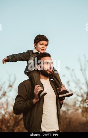 Petit garçon assis sur les épaules du père sur fond de ciel bleu.