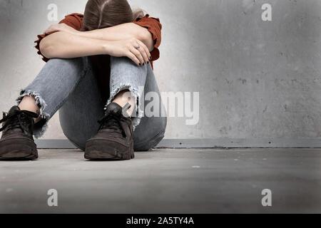 Jeune femme pleure et s'assis près d'un mur vide, triste et déprimé lonely girl holding sa tête vers le bas Banque D'Images