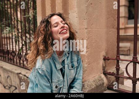 Jeune femme avec des cheveux bouclés et lunettes dans la ville