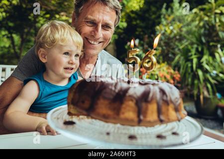 Petit garçon assis sur les genoux du père, qui fête son anniversaire