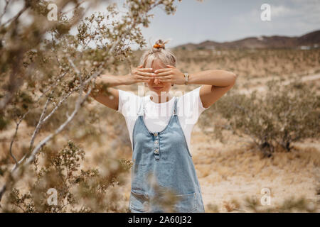 Young woman standing in desert landscape, Joshua Tree National Park, California, USA