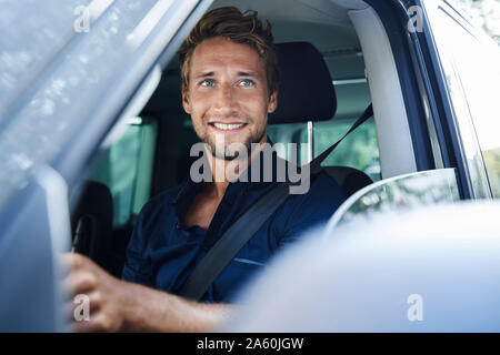 Smiling young man in car Banque D'Images