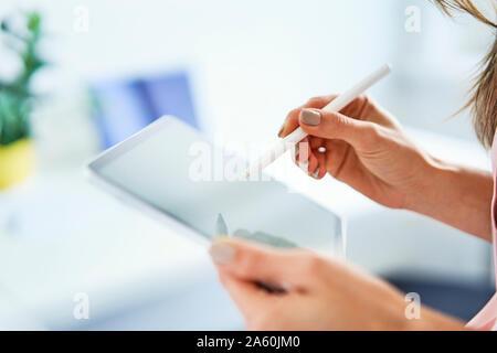 Close up of woman en utilisant un stylo et tablet in office