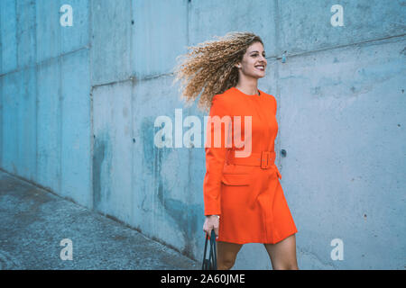 Happy young woman wearing red dress marcher le long street Banque D'Images
