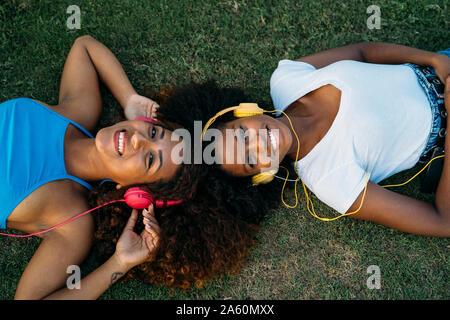 Portrait de deux jeunes femmes heureux couché sur la musique avec un casque d'écoute meadow Banque D'Images