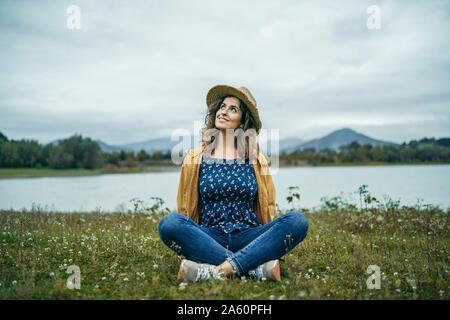 Young smiling woman wearing manteau jaune assis sur un pré et jusqu'à la