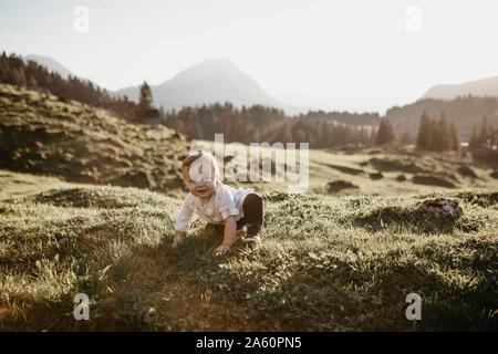 Petit garçon heureux de ramper sur une prairie alpine, Schwaegalp, Nesslau, Suisse