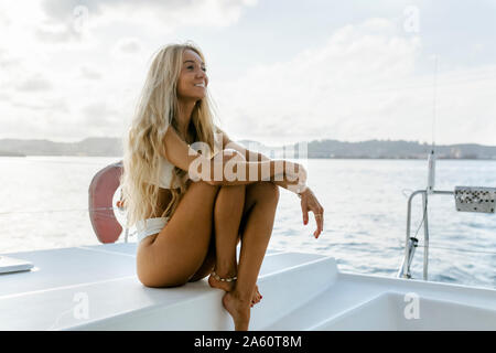 Young smiling woman sitting on a sailboat