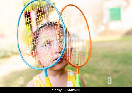 Petite fille jouant avec des raquettes de badminton en plein air en été